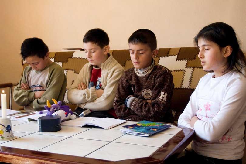 Children saying prayers at a devotional gathering