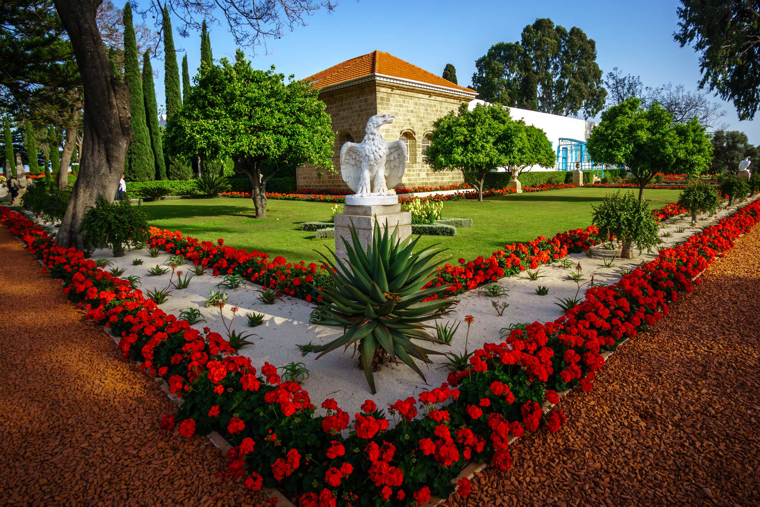 Corder view of the Shrine of Baha'u'llah with red flowers and a eagle statue
